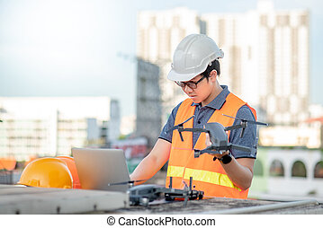 Asian man using drone and laptop for construction site survey