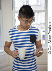 Asian Man using his phone at home in the lounge.