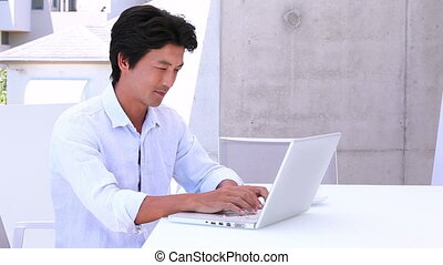 Asian man using laptop and answering phone - Asian man using...