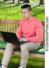Asian man using laptop in garden