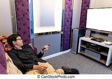 Asian man using remote controller while watching TV