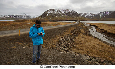 Asian man using smart phone for internet gps for road trip and social media during journey in Iceland