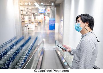 Asian man using smartphone in supermarket
