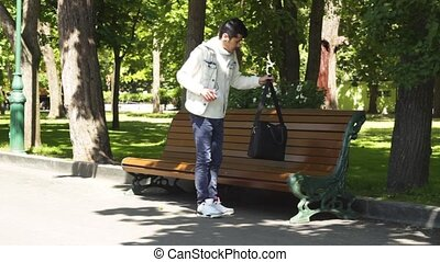 Asian man walking in park and sitting down on bench for resting and drinking bevarage