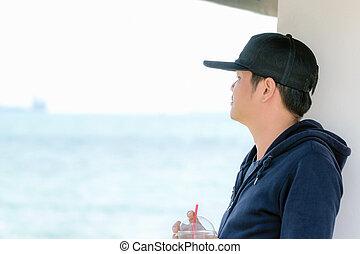Asian man wearing a blue long sleeve shirt and wearing a hat.