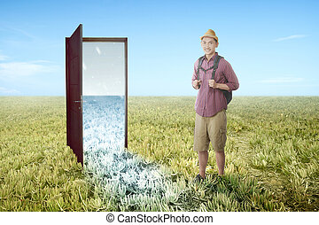 Asian man with backpack standing in front of the opened door from summer to winter climate on the meadow field