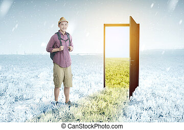 Asian man with backpack standing in front of the opened door from winter to summer climate on the meadow field