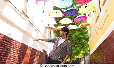 Asian man with earphones is dancing outdoor in summer day...
