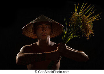 Asian man with sheaf of rice