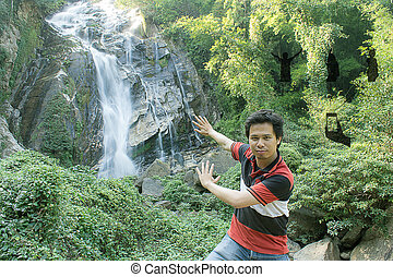 asian man with social network of friends and clients at Mae Tia Waterfall Chiangmai Thailand