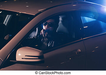 Asian man with sunglasses in car at night.