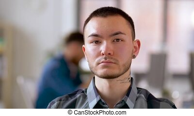 asian man with tattoo and ear tunnel at office - business...
