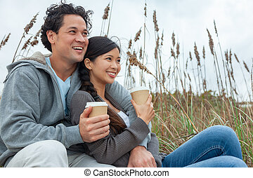 Asian Man Woman Romantic Couple Drinking Takeout Coffee on Beach