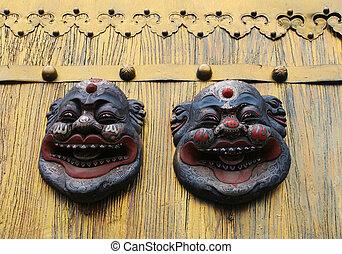 Asian masks on a gold door