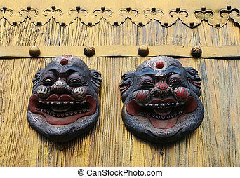 Asian masks on a gold door