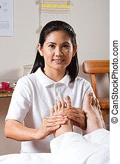 asian masseuse foot massage