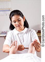 asian masseuse giving foot massage