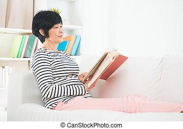 asian matured senior woman reading on a sofa