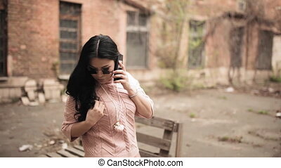 Middle-aged Asian model in pink clothes and stylish designer sunglasses stands against the background of an old factory. She speaks on the phone and plays with her hair.