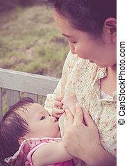 mom breast feeding her baby girl in park