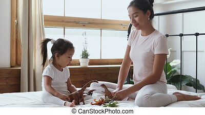 Asian mom with kid daughter playing toys sit in bed