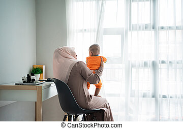 Asian moslem mother holding her little boy on lap when playing together
