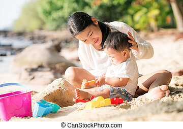Asian mother and baby play sand and toy togather