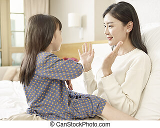 asian mother and child having a good time chatting at home