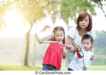 Asian mother and children playing at outdoor park.