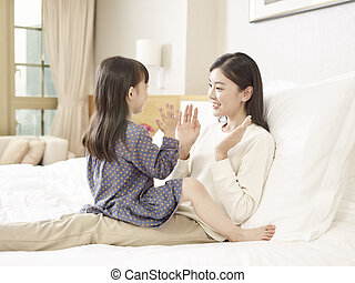 asian mother and daughter having a good time chatting playing