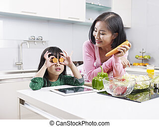 asian mother and daughter in kitchen