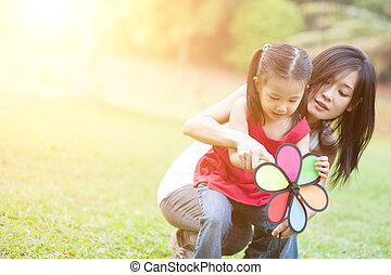 Asian mother and daughter playing windmill at outdoors.