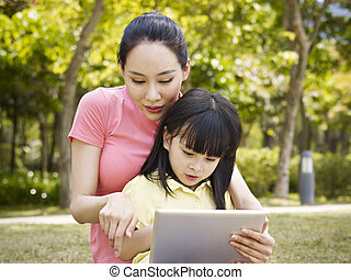 asian mother and daughter using tablet computer