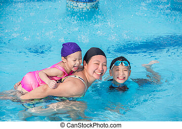 mother and her childrean happy in swimming pool together