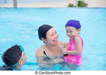 mother and her children happy in swimming pool together