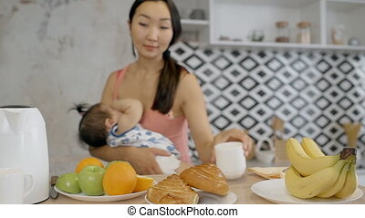 Asian mother breasfeeding her baby and putting mugs