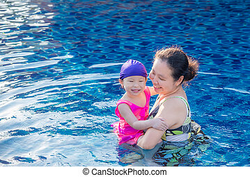 mother Holding her daughter in the pool with a happy smile.