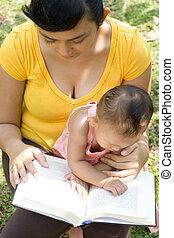 asian mother reading while babysitting