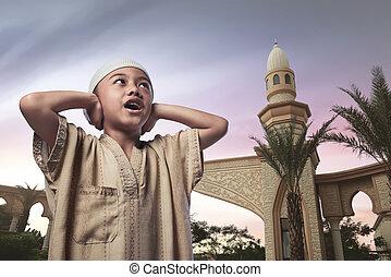 Asian muslim child with traditional dress praying