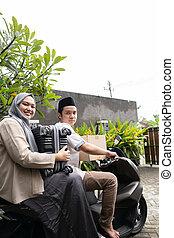 Asian Muslim couples with motorbike mudik carrying lots of items