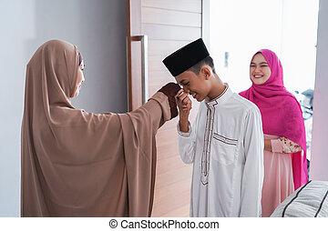 asian muslim parent shake hand in idul fitri eid mubarak...