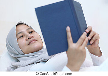 Asian muslim woman reading holy Quran on bed, reciting to ...