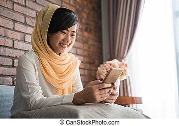 muslim woman using mobile phone at home sitting