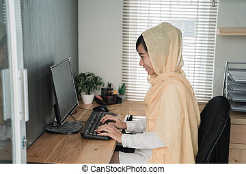 asian muslim woman working in her office