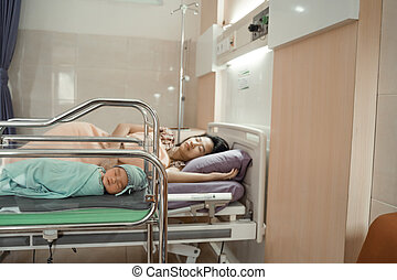 Asian newborn baby laying in crib with his mother lying on bed side