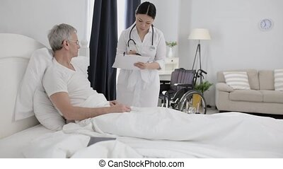Asian nurse assists disabled senior man in bed