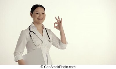 Asian Nurse on White Background Smiles and Lifts Thumb. -...