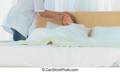 Asian nurse taking her patient's temperature
