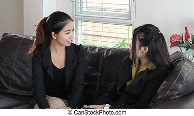 Asian Office Coworkers Talking - An attractive Asian woman...
