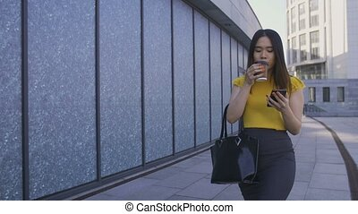Asian office worker using phone, drinking coffee - Gorgeous...